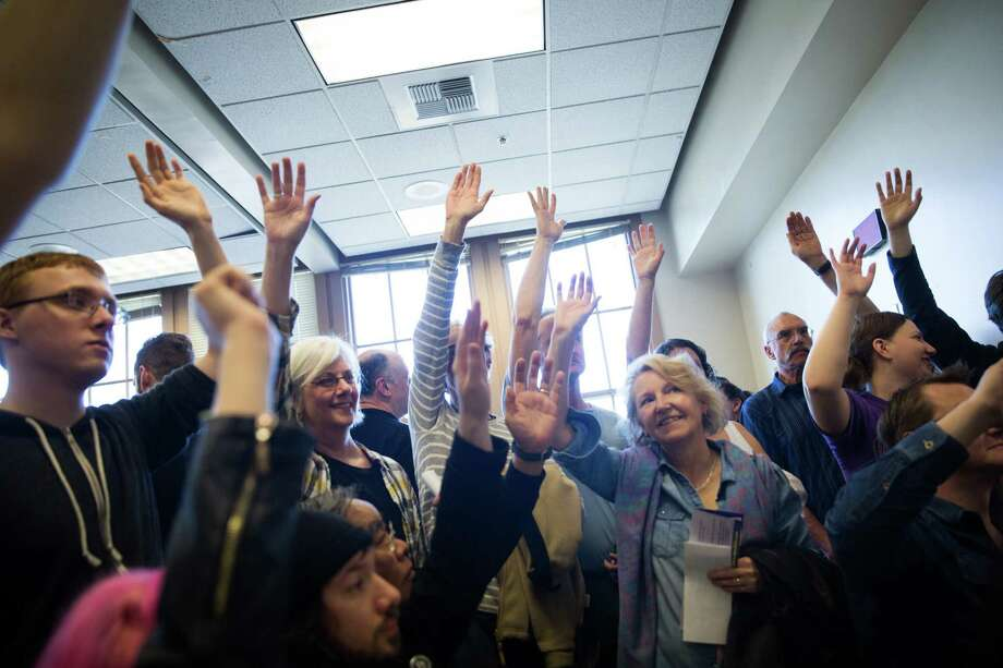 Voters raise their hands in support of democratic presidential candidate Bernie Sanders during the democratic caucus at Tops K-8 School on Saturday, Mar. 26, 2016. Photo: GRANT HINDSLEY, SEATTLEPI.COM / SEATTLEPI.COM