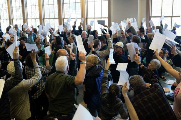 Voters raise their hand to signify their decision during the democratic caucus at Tops K-8 School on Saturday, Mar. 26, 2016.