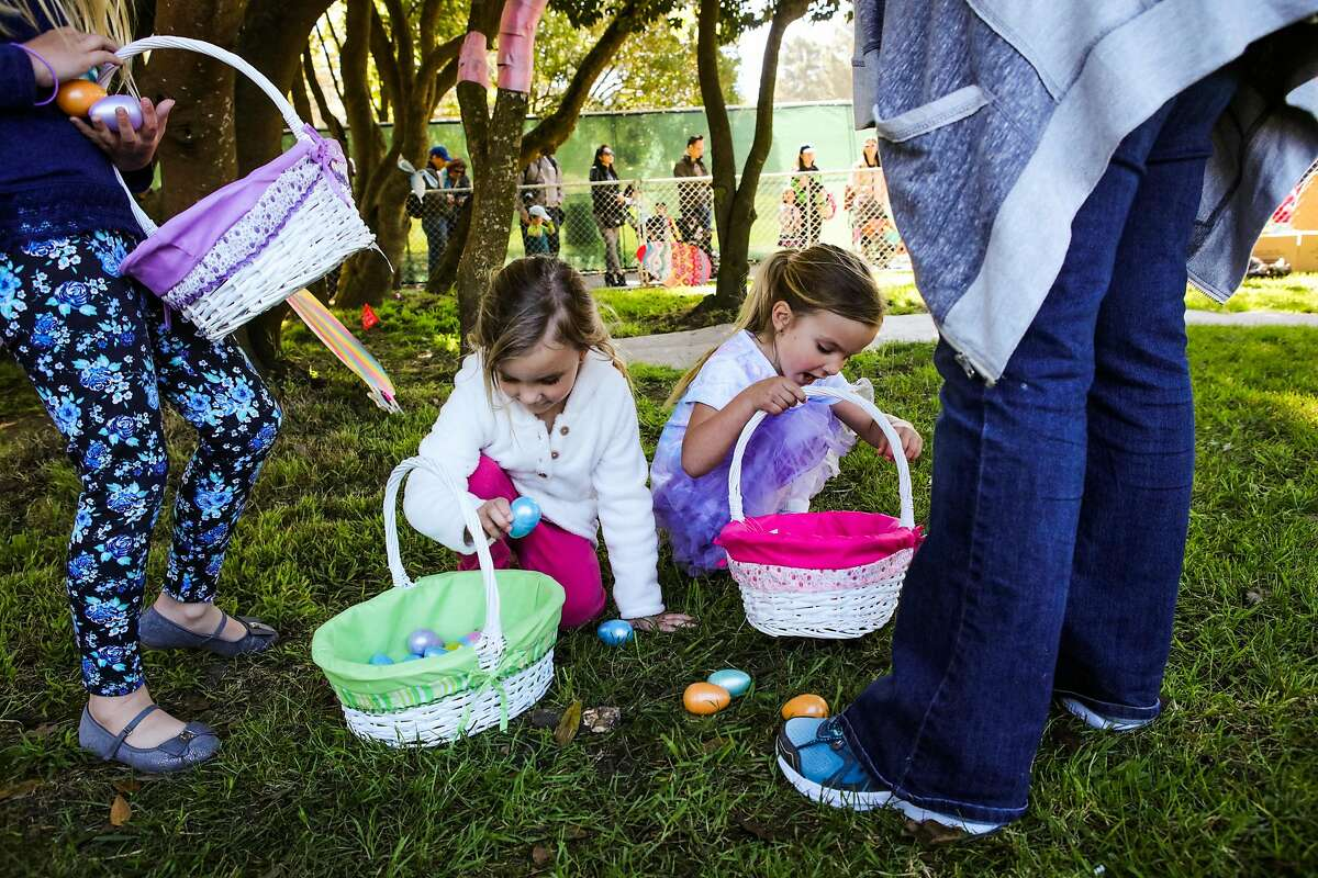 Sisters Olivia Shaal, 8, Lauren Schaal, 4 and Emma Schaal, 4, go through their easter egg baskets at Golden Gate Park, in San Francisco, California, on Saturday, March 26, 2016.