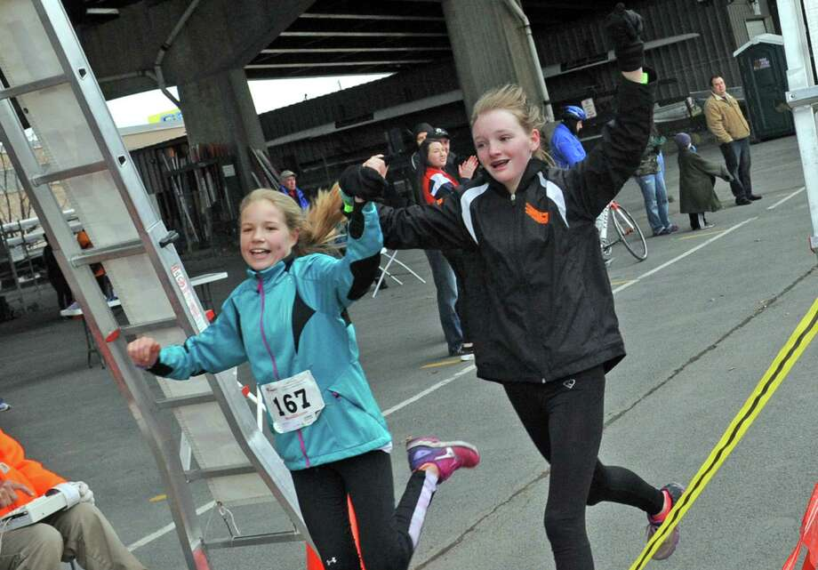 Rachel Hodge, 13 left, and Emily Smith, 13, both of Delmar cross the finish line during the Ice Breaker Challenge 5K at the Corning Preserve on Saturday March 26, 2016 in Albany, N.Y. (Michael P. Farrell/Times Union) Photo: Michael P. Farrell / 20035945A