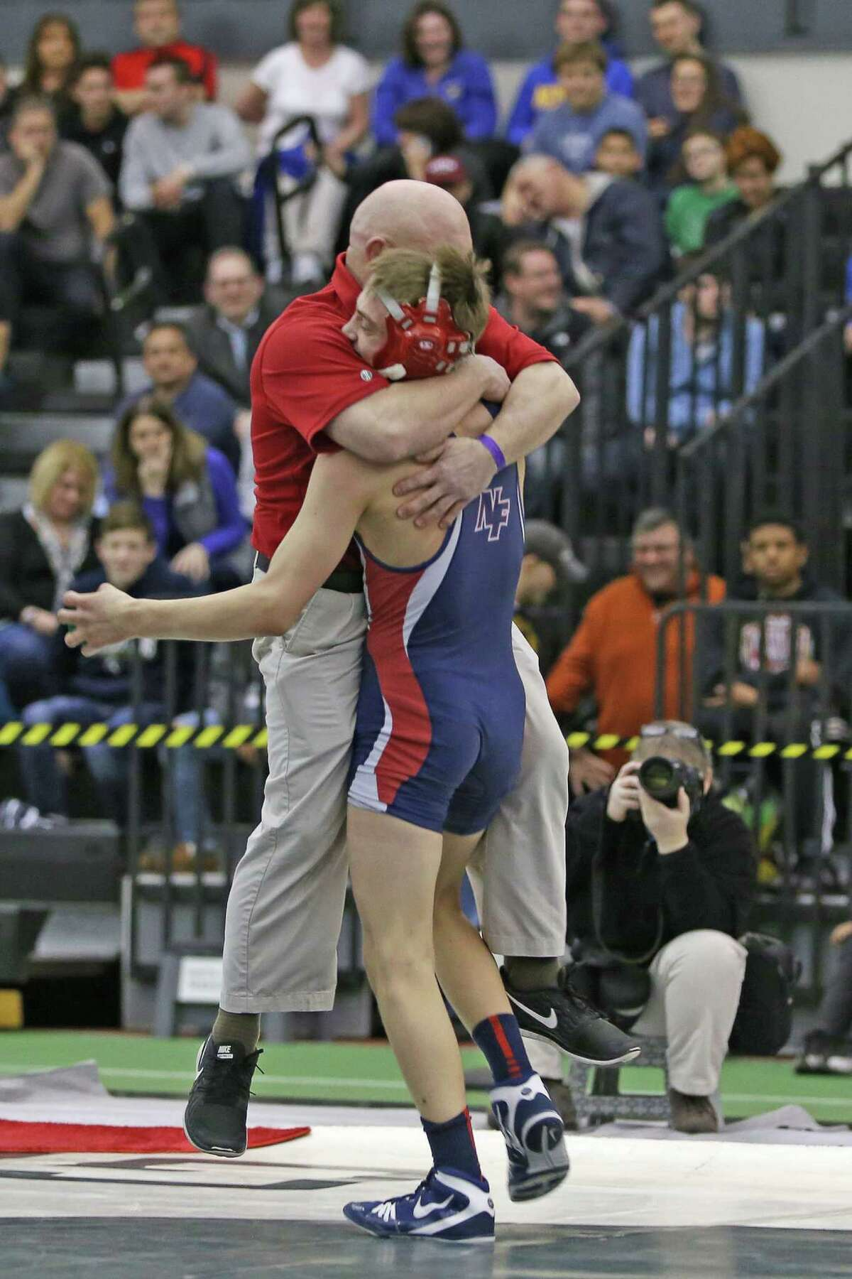 New Fairfield High School's Alec Opsal celebrates with coach Paul Musso after his win at 120 pounds during the State Open wrestling championships at Flyod Little Athletic Center in New Haven last month.