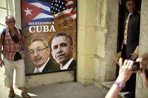 A tourist poses with a Raul Castro-Barack Obama picture outside a restaurant in Havana. A group of Texas leaders is advocating wider trade and travel between the U.S. and Cuba.