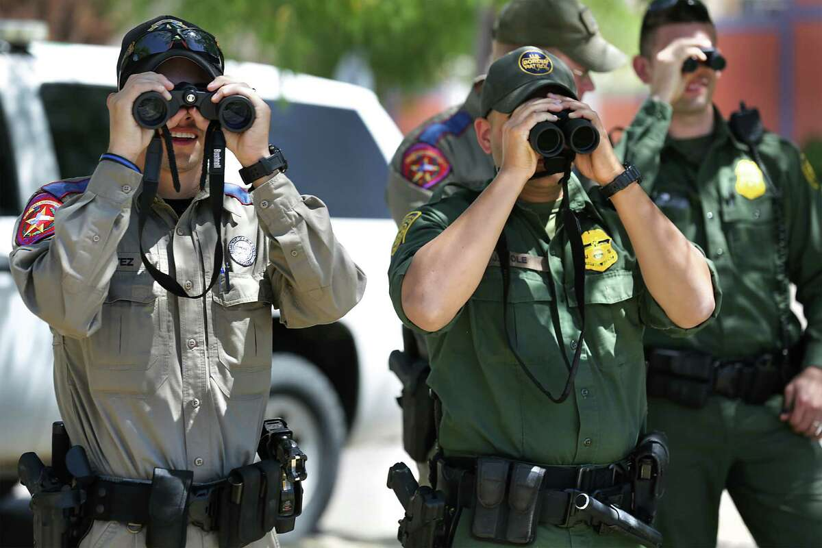 Texas State Troopers of the Department of Public Safety and Border Patrol agents watch preparations for weekend Easter activities in Ciudad Miguel Aleman, MX across the border from Roma, TX on Thursday, March 24, 2016. DPS is making their presence known in the Rio Grande Valley.