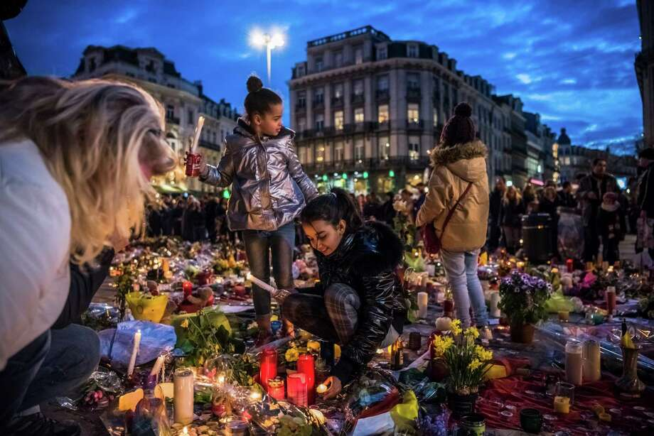 "Children light candles as people pay their respects at a makeshift memorial for victims of multiple attacks, at Place de la Bourse in Brussels, March 26, 2016 On Saturday, the airport was still closed, a huge and macabre crime scene instead of a global crossroads and the main entry point to the ""capital of Europe,"" a city that houses the headquarters of the European Union and NATO. (Daniel Berehulak/The New York Times) ORG XMIT: XNYT20 Photo: DANIEL BEREHULAK / NYTNS"