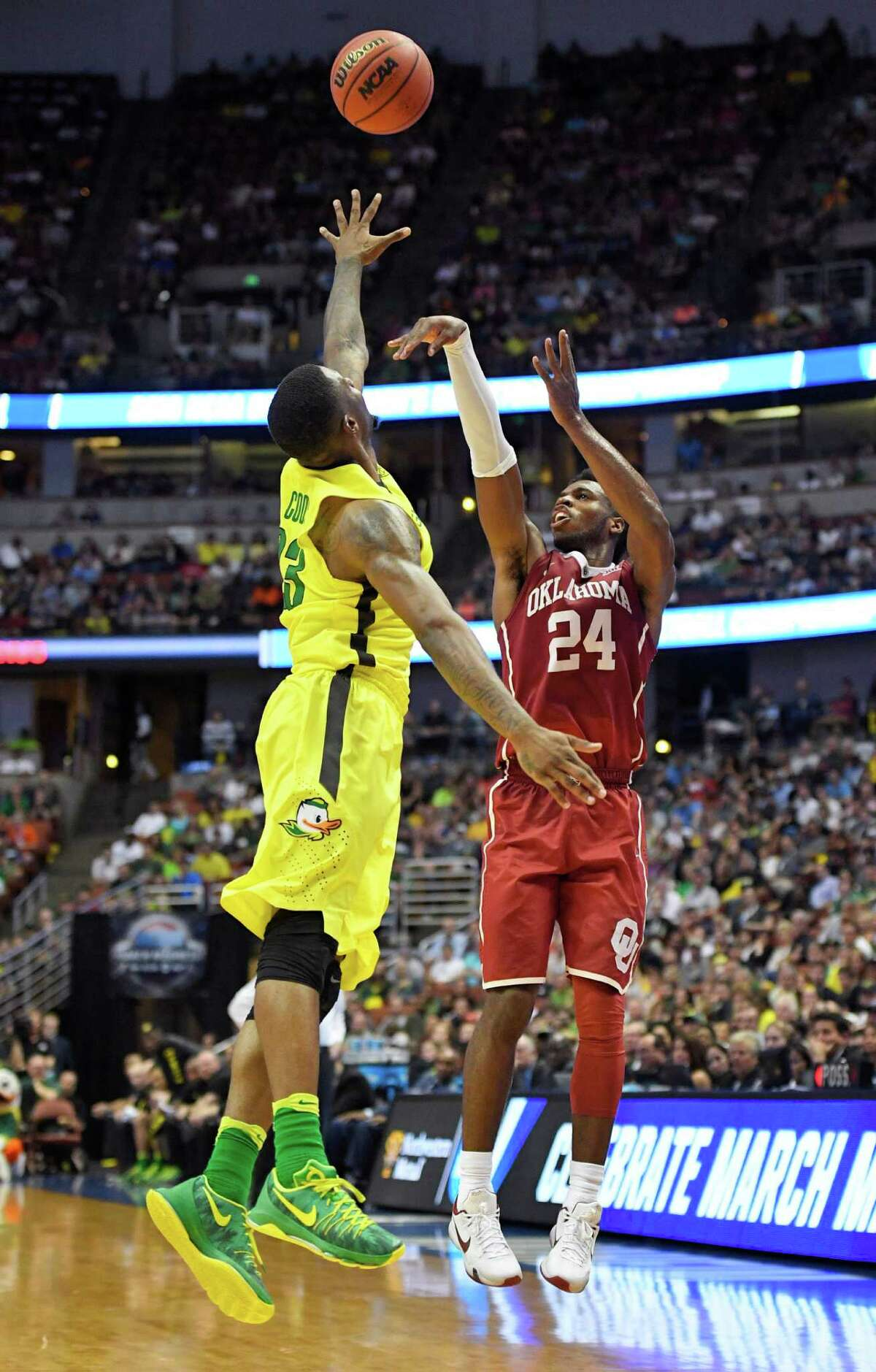Oklahoma guard Buddy Hield scores over Oregon forward Elgin Cook during the second half of an NCAA college basketball game in the regional finals of the NCAA Tournament, Saturday, March 26, 2016, in Anaheim, Calif.