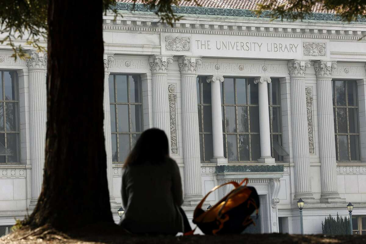 A student sits in the shade in front of the University of California Library on the Cal campus in Berkeley, CA Wednesday, February 11, 2016.