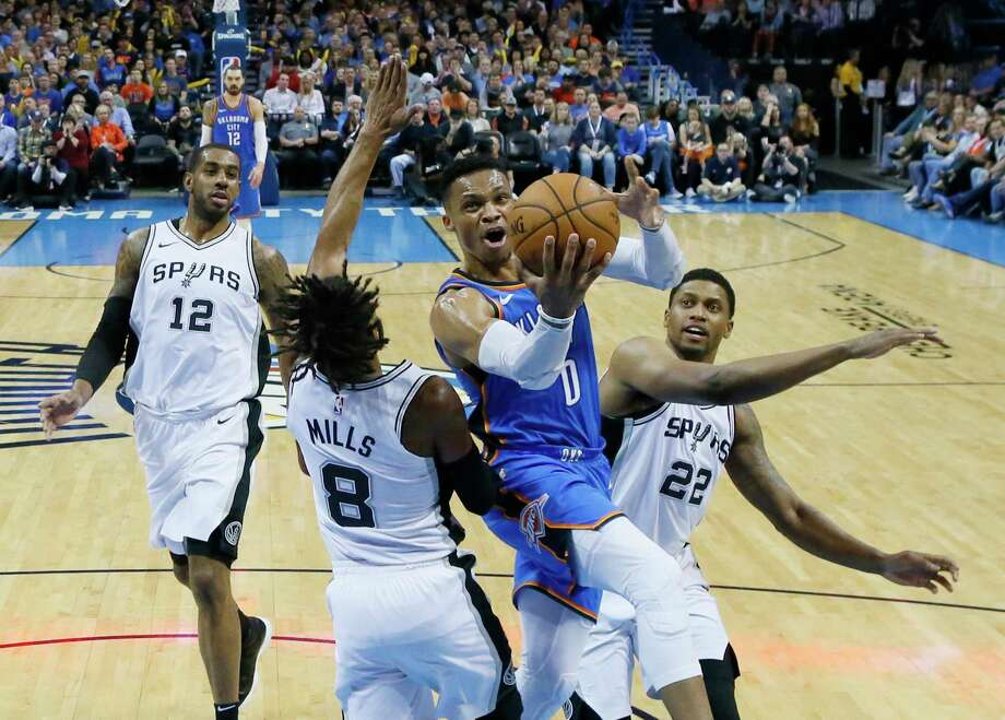Oklahoma City Thunder guard Russell Westbrook (0) goes to the basket between San Antonio Spurs guard Patty Mills (8) and forward Rudy Gay (22) in the first half of an NBA basketball game in Oklahoma City, Saturday, March 10, 2018. (AP Photo/Sue Ogrocki) Photo: Sue Ogrocki, Associated Press / AP2018