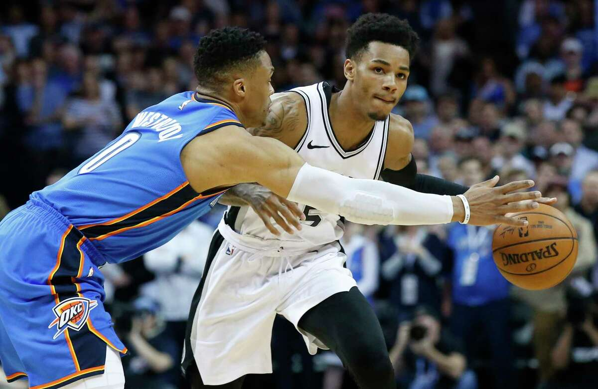 Oklahoma City Thunder guard Russell Westbrook (0) reaches for the ball as San Antonio Spurs guard Dejounte Murray, right, dribbles in the first half of an NBA basketball game in Oklahoma City, Saturday, March 10, 2018. (AP Photo/Sue Ogrocki)