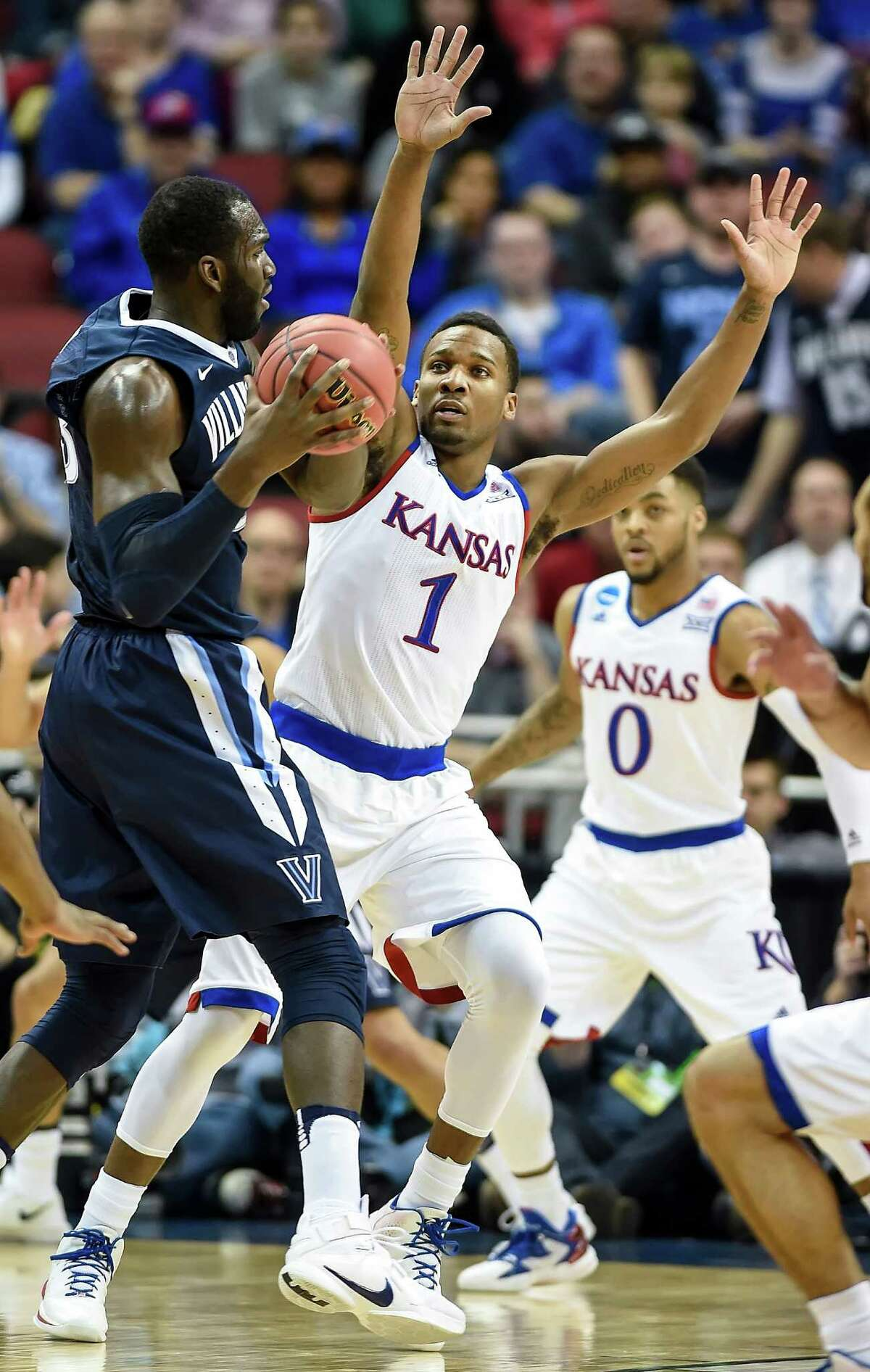 Kansas guard Wayne Selden Jr. (1) pressures Villanova forward Daniel Ochefu, left, in the first half during the finals of the NCAA Tournament's South region at the KFC Yum! Center in Louisville, Ky., on Saturday, March 26, 2016.