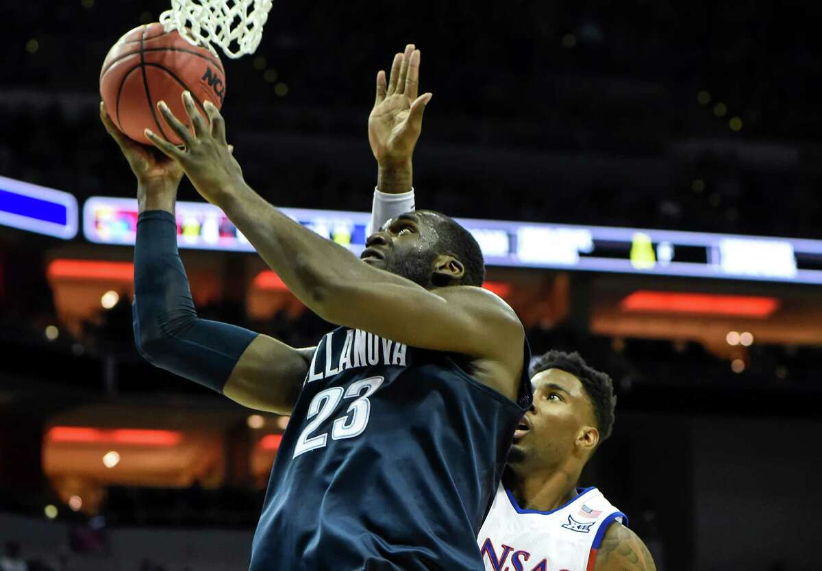 Villanova forward Daniel Ochefu (23) drives to the basket past Kansas forward Jamari Traylor in the first half during the finals of the NCAA Tournament's South region at the KFC Yum! Center in Louisville, Ky., on Saturday, March 26, 2016.