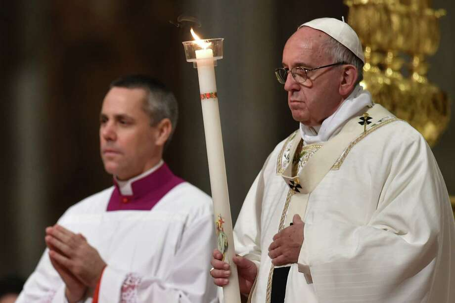Pope Francis leads the Easter Vigil on Saturday at St. Peter's Basilica in the Vatican. Christians around the world are marking the Holy Week, commemorating the crucifixion of Jesus Christ, leading up to his resurrection on Easter.  Photo: ALBERTO PIZZOLI, Staff / AFP