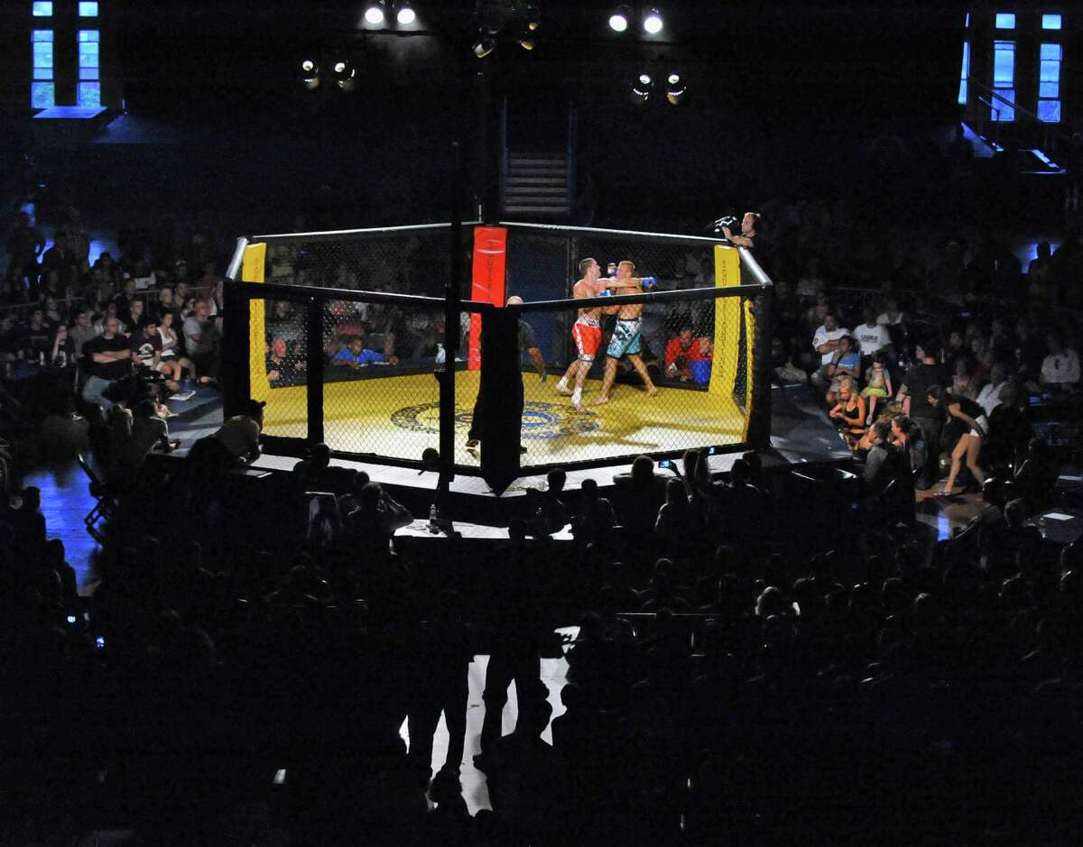 Chad Niles, in the red trunks, and Mike Guynup during the 195-200 Lb. class match at an Amateur Mixed Martial Arts event at the Washington Avenue Armory in Albany Saturday Aug. 11, 2012. Beretz went on to win. (John Carl D'Annibale / Times Union)