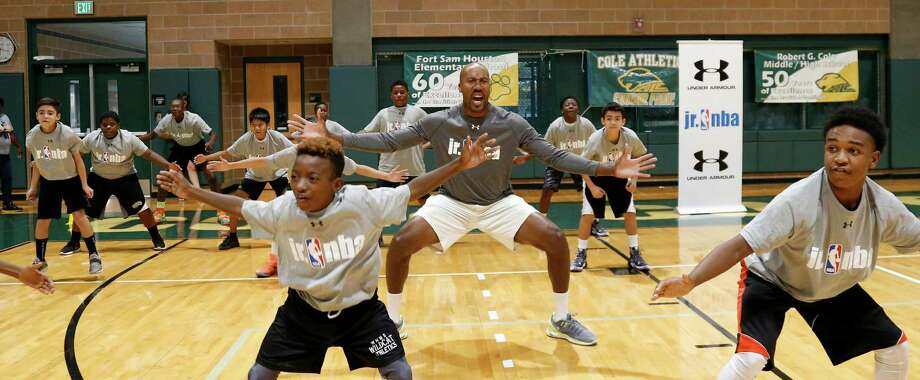 Former Spur Bruce Bowen leads kids in a drill at the NBA Tipoff Inaugural Junior Clinic at Cole High School in 2015. Photo: Ron Cortes /For The Express-News