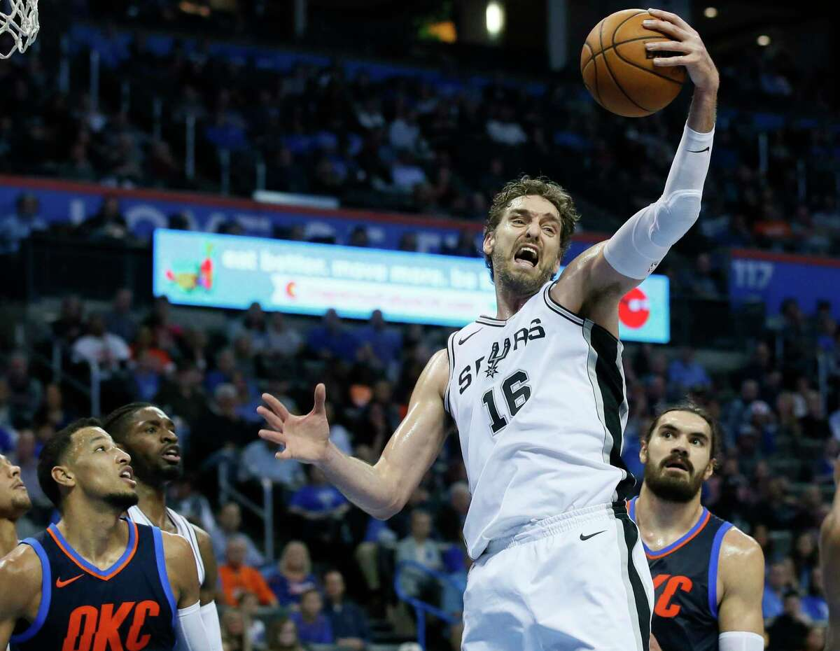 San Antonio Spurs center Pau Gasol (16) grabs a rebound between Oklahoma City Thunder guard Andre Roberson, left, and center Steven Adams, right, in the second quarter of an NBA basketball game in Oklahoma City, Sunday, Dec. 3, 2017. (AP Photo/Sue Ogrocki)