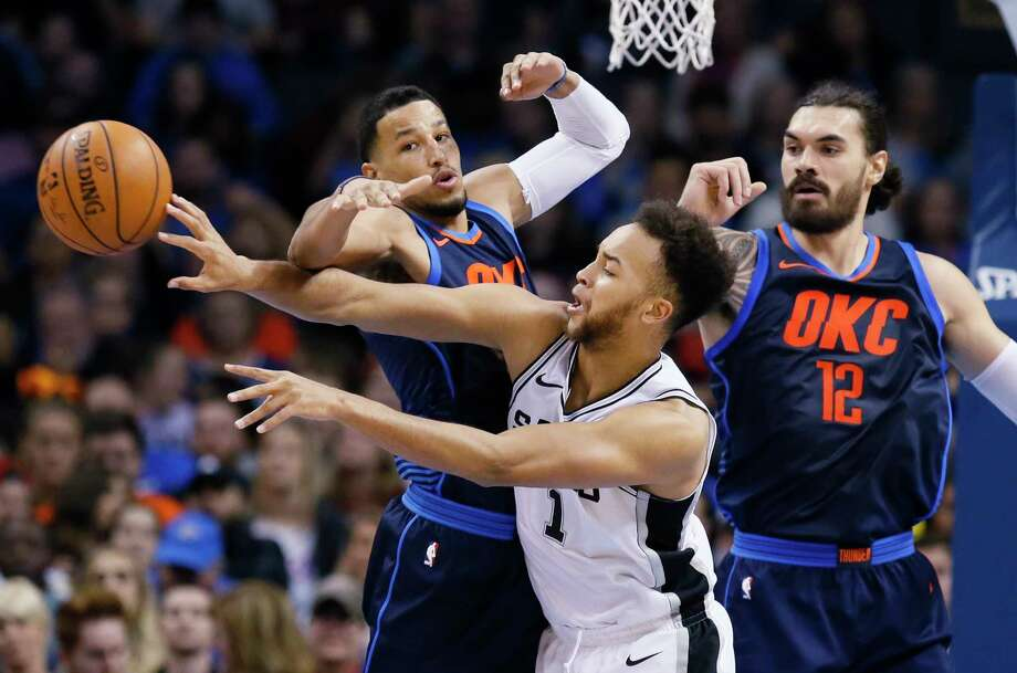 San Antonio Spurs forward Kyle Anderson (1) passes the ball in front of Oklahoma City Thunder guard Andre Roberson, left, and center Steven Adams (12) during the second quarter of an NBA basketball game in Oklahoma City, Sunday, Dec. 3, 2017. (AP Photo/Sue Ogrocki) Photo: Sue Ogrocki, Associated Press / AP2017