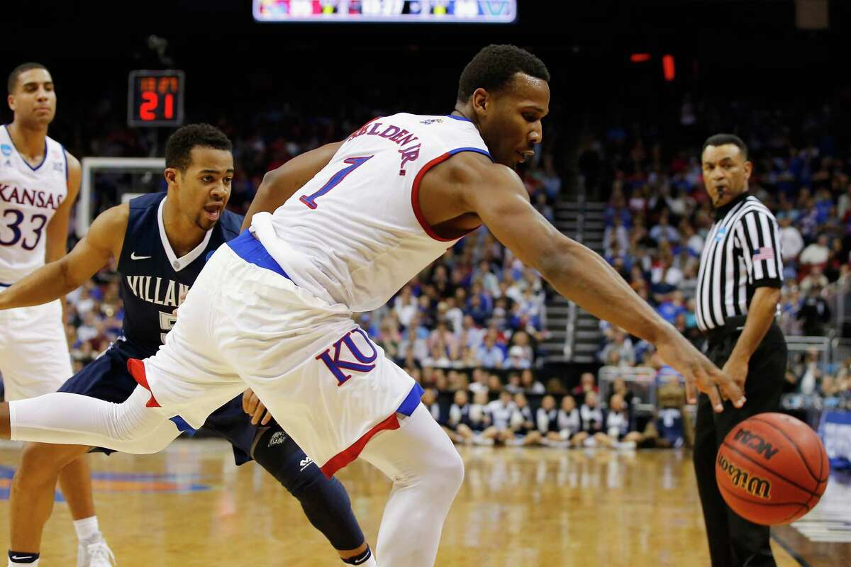 LOUISVILLE, KY - MARCH 26: Wayne Selden Jr. #1 of the Kansas Jayhawks prevents the ball from going out of bounds in the second half against the Villanova Wildcats during the 2016 NCAA Men's Basketball Tournament South Regional at KFC YUM! Center on March 26, 2016 in Louisville, Kentucky.