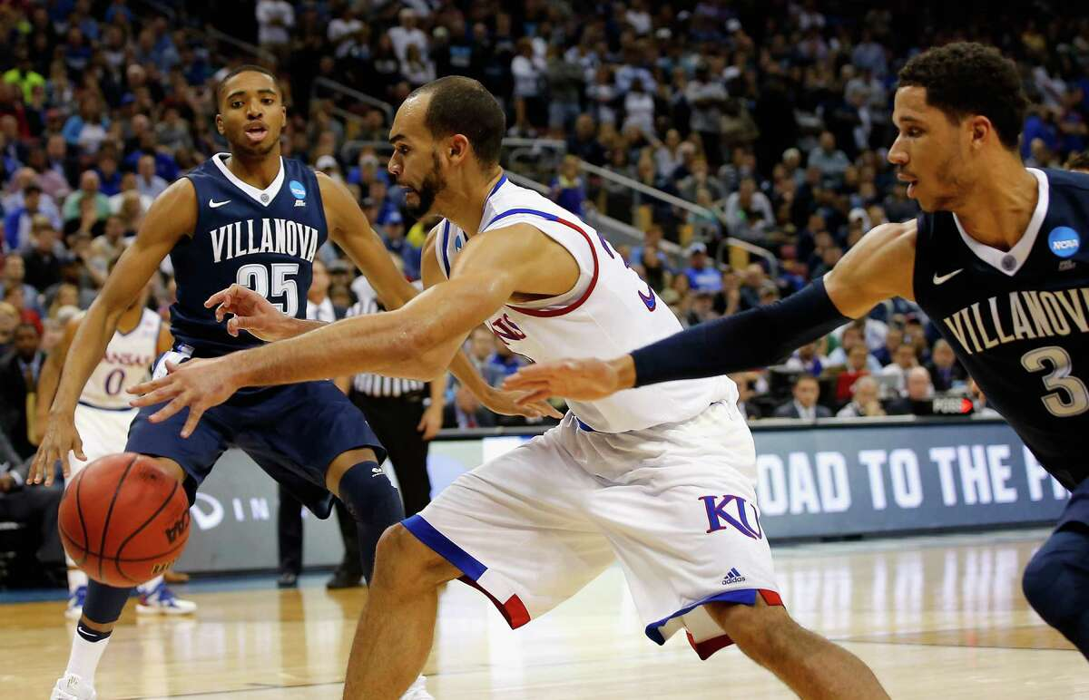 LOUISVILLE, KY - MARCH 26: Perry Ellis #34 of the Kansas Jayhawks handles the ball against Mikal Bridges #25 of the Villanova Wildcats and Josh Hart #3 in the second half during the 2016 NCAA Men's Basketball Tournament South Regional at KFC YUM! Center on March 26, 2016 in Louisville, Kentucky.