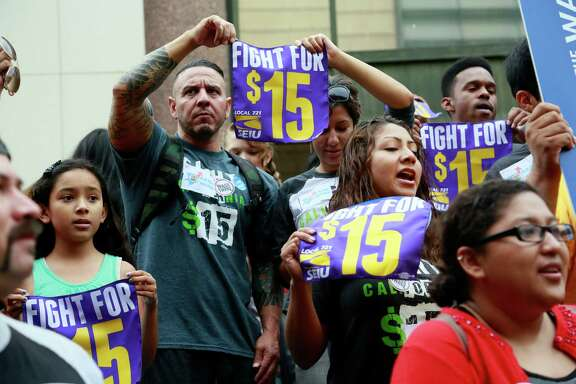 FILE - In this Tuesday, July 21, 2015 file photo, workers hold a rally in Los Angeles in support of the Los Angeles County Board of Supervisors' proposed minimum wage ordinance. On Saturday, March 26, California legislators and labor unions reached an agreement that will take the state's minimum wage from $10 to $15 an hour.