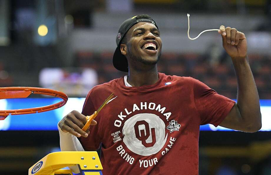 Buddy Hield cuts down the net that he just torched for 37 points in a win over top-seeded Oregon that sends the Sooners to Houston for the Final Four. Photo: Mark J. Terrill, AP