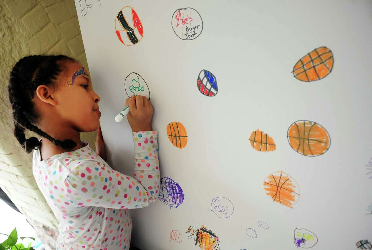 Tatyana Gloria Reyes, 8, of Bridgeport, draws while at the Arcade Mall's Fan Fest which was held to welcome visitors attending the NCAA Basketball Championship at the Arena at Harbor Yard in downtown Bridgeport, Conn., on Saturday March 26, 2016. Activities included music by DJ Bongo Joe and his live band Off the Hook, face painting, caricatures, and food was provided from several downtown restaurants.