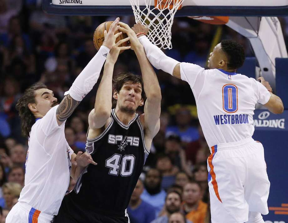 Oklahoma City Thunder center Steven Adams, left, San Antonio Spurs center Boban Marjanovic (40) and guard Russell Westbrook (0) reach for a rebound in the third quarter of an NBA basketball game in Oklahoma City, Saturday, March 26, 2016. Oklahoma City won 111-92. (AP Photo/Sue Ogrocki) Photo: Sue Ogrocki, STF / AP / AP