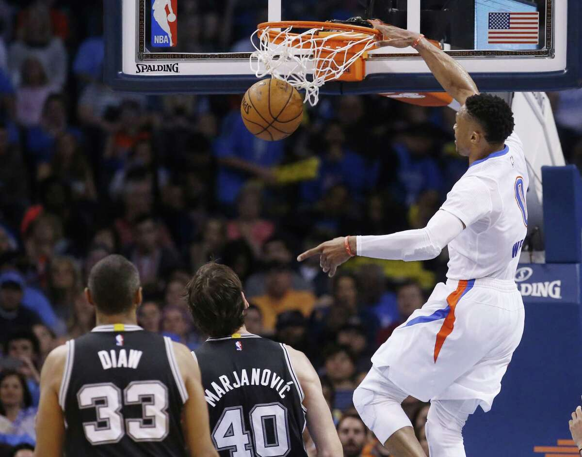 Thunder guard Russell Westbrook dunks in front of San Antonio Spurs center Boris Diaw (33) and center Boban Marjanovic (40) in the third quarter in Oklahoma City on March 26, 2016.
