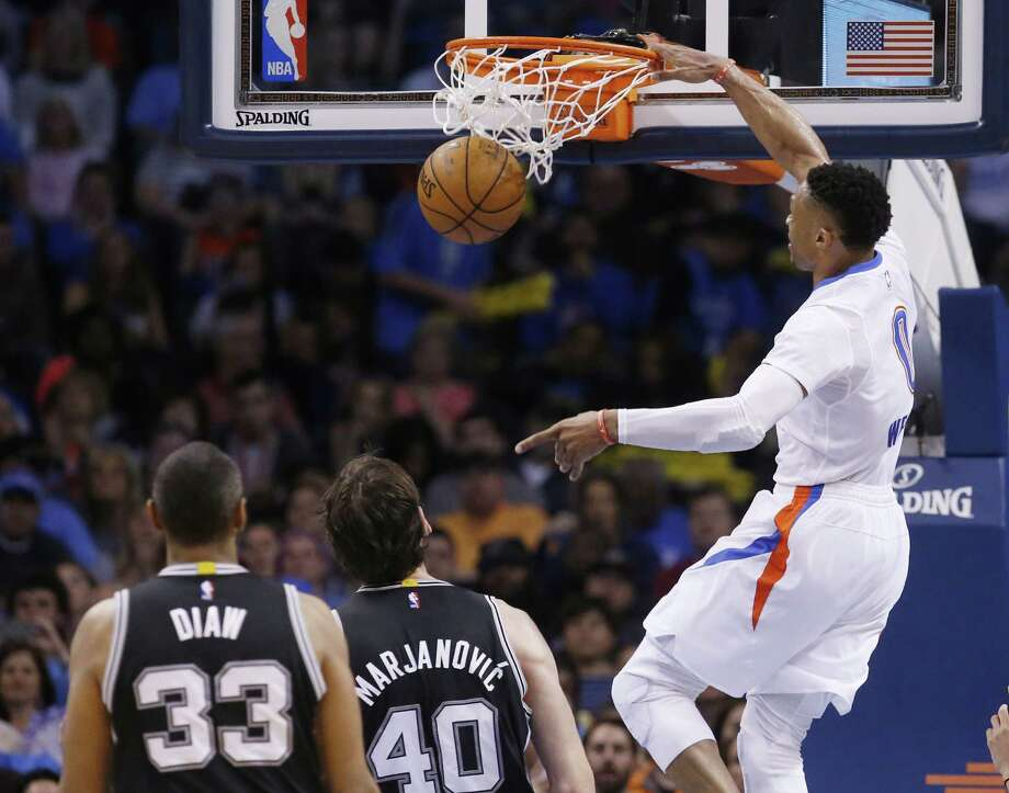 Thunder guard Russell Westbrook dunks in front of San Antonio Spurs center Boris Diaw (33) and center Boban Marjanovic (40) in the third quarter in Oklahoma City on March 26, 2016. Photo: Sue Ogrocki /AP / AP