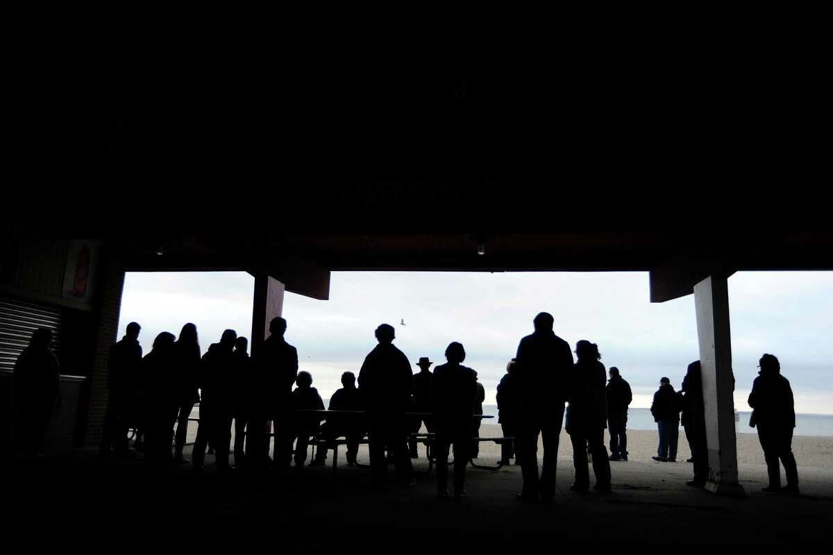 People gather inside the East Pavilion of Cove Island Beach to listen to Pastor Jack Breznen give an Easter sunrise mass on Sunday, March 27, 2016 in Stamford, Conn.