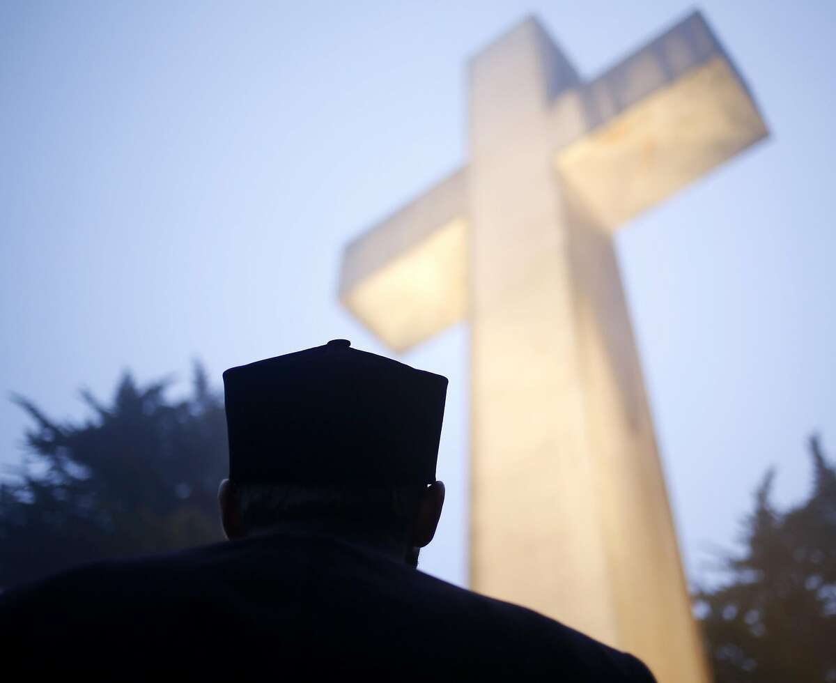 Father Mesrop Ash of St. John Armenian Apostolic Church looks up at the Mount Davidson Cross before Easter sunrise service in San Francisco, California, on Sunday, March 27, 2016.
