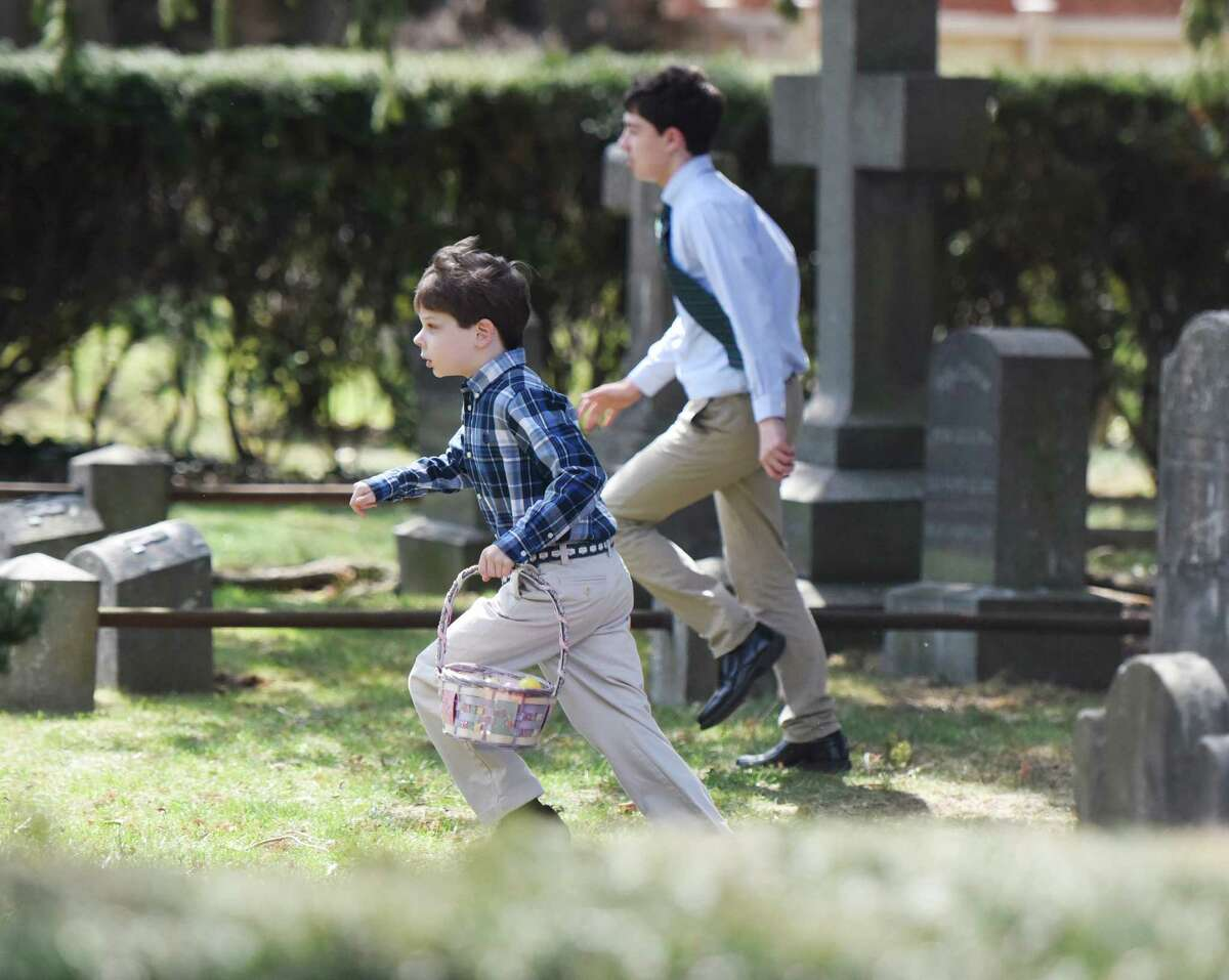 Third-grader Ethan Cooper, of Greenwich, runs with his Easter basket to collect eggs during the Easter egg hunt in the memorial garden at Christ Church in Greenwich, Conn. Sunday, March 27, 2016. Before the egg hunt, hundreds attended Easter mass to celebrate the resurrection of Jesus Christ and the gifts of life and love that are believed to be given through the resurrection.