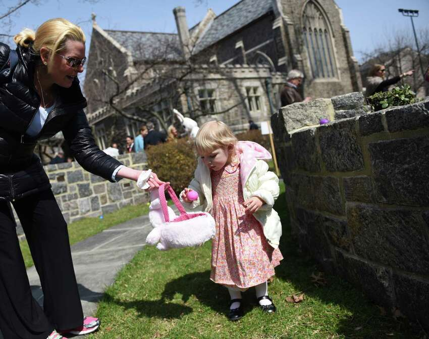Alexandra Setterberg, 2, of Greenwich, collects eggs during the Easter egg hunt in the memorial garden at Christ Church in Greenwich, Conn. Sunday, March 27, 2016. Before the egg hunt, hundreds attended Easter mass to celebrate the resurrection of Jesus Christ and the gifts of life and love that are believed to be given through the resurrection.