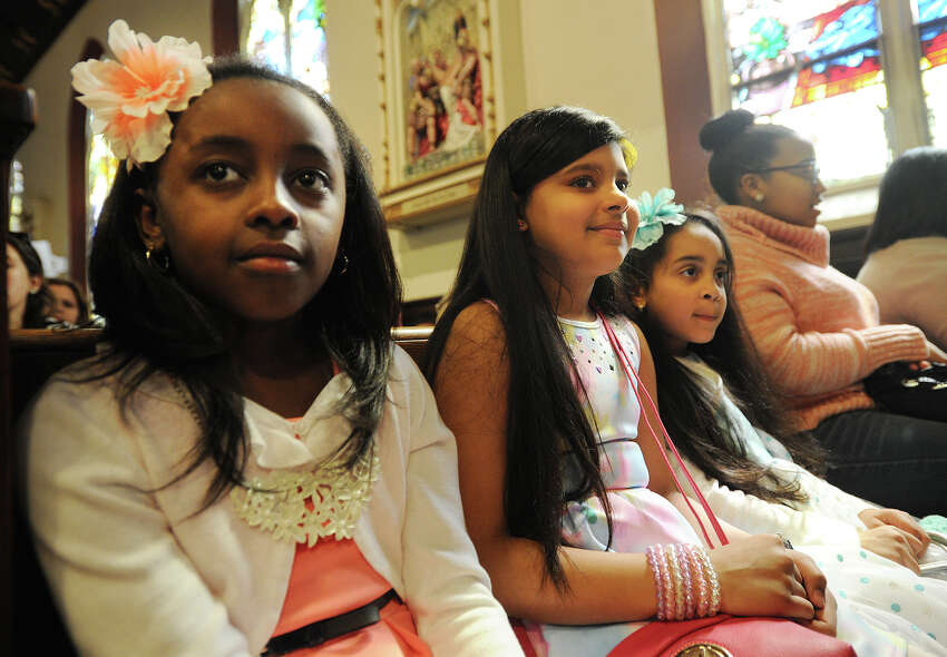 From left; Yulisa Romero, 9, Taishaly Casillas, 9, and Edelys Jorge, 6, all of Bridgeport, wear their Easter dresses and flowers in their hair to Easter services at St. Charles Borromeo Catholic Church on East Main Street in Bridgeport, Conn. on Sunday, March 27, 2016.