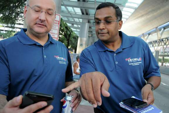 Metro chairman Gilbert Garcia and Metro board member Sanjay Ramabhadran  use the new app to check arrival times for buses at the Downtown Transit Center Sunday August 16, 2015. The group was celebrating the rollout of the new Metro network.(Dave Rossman photo)
