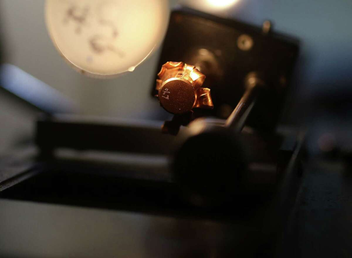 A bullet is examined under a microscope at the forensics department located inside the Houston Police Department on Tuesday, March 22, 2016, in Houston.