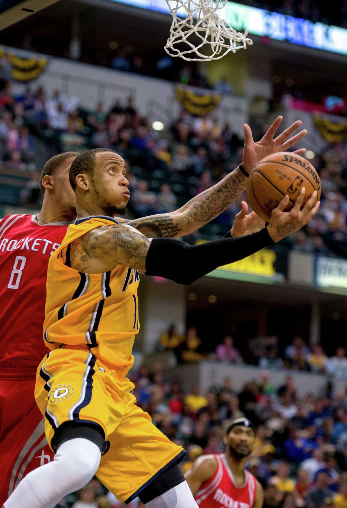 Indiana Pacers guard Monta Ellis (11) slips under the basket for a reverse lay-up attempt as he's defended by Houston Rockets forward Michael Beasley (8) during the second half of an NBA basketball game, Sunday, March 27, 2016, in Indianapolis. The Pacers won 104-101.