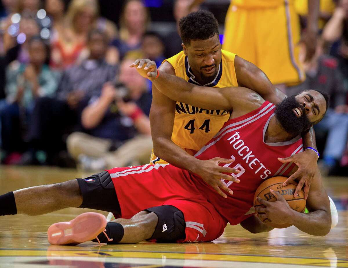 Houston Rockets guard James Harden (13) grimaces as he battles for the loose ball with Indiana Pacers forward Solomon Hill (44) during the second half of an NBA basketball game, Sunday, March 27, 2016, in Indianapolis. The play resulted in a jump ball. The Pacers won 104-101.