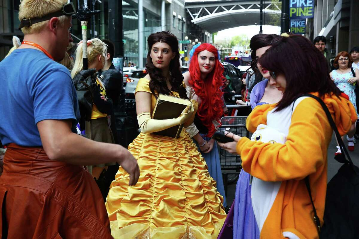 Kylie Dejong, dressed as Belle, and Anna Dejong, dressed as Ariel, wait in line at a crepe shop outside Sakura-Con, at the Washington State Convention Center, Sunday, Mar. 27, 2016.