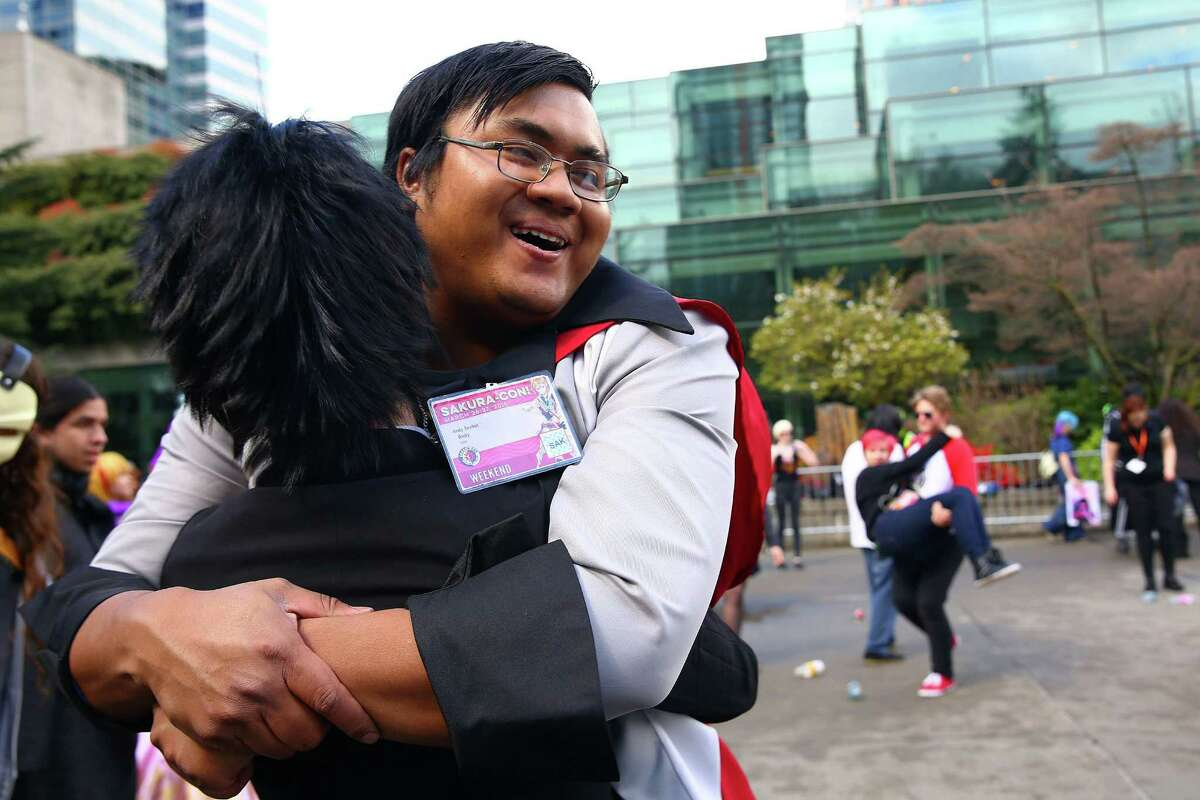 Andy Senket gets a hug during a game participants played outside SakuraCon anime convention, Sunday, Mar. 27, 2016 at the Washington State Convention Center.