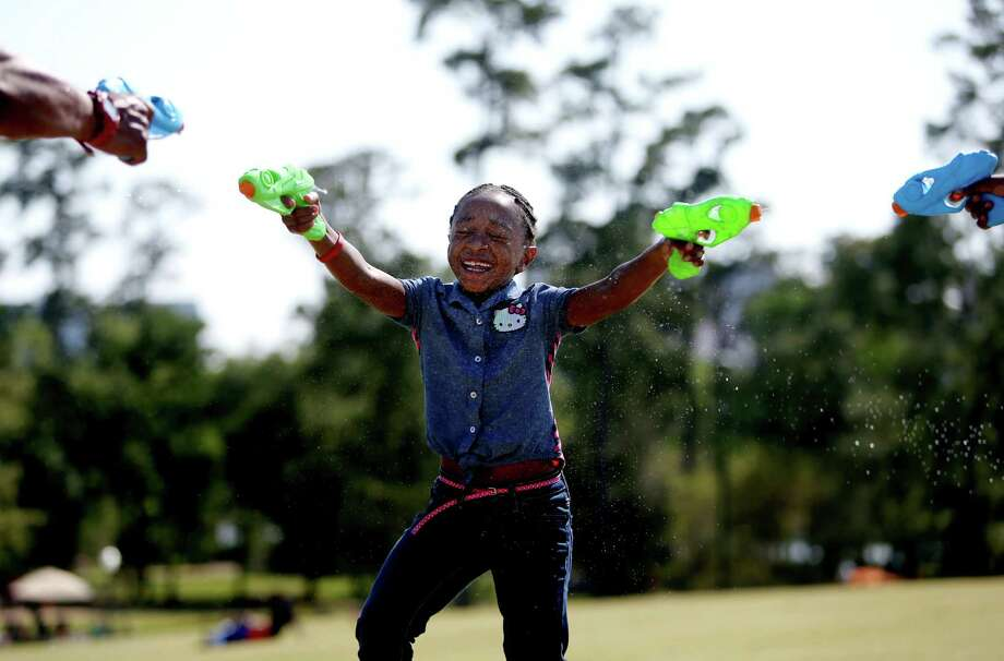 Kyleigh Turner, 6, has a squirt gun battle with father Torey Butler, and sister Jayia Turner, 10, on Easter at Hermann Park Sunday, March 27, 2016, in Houston. The sisters spent the day with their father Torey Butler, of Houston, flying kites, blowing bubbles and having squirt gun battles. Photo: Gary Coronado, Houston Chronicle / © 2015 Houston Chronicle