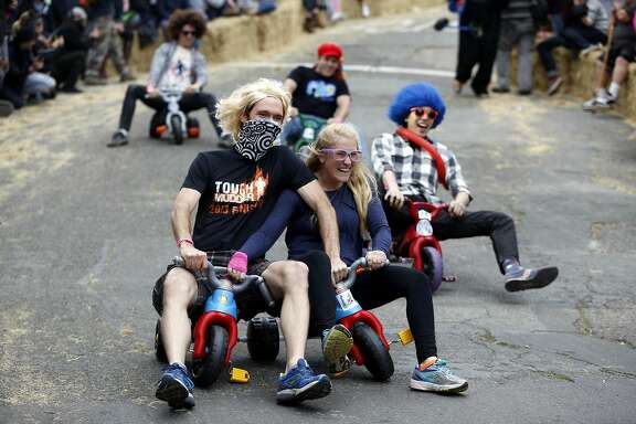 A couple navigate each other's tricycles during the Bring Your Own Big Wheel race in San Francisco, California, on Sunday, March 27, 2016.