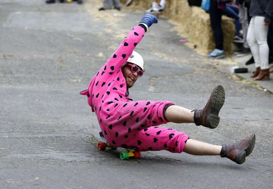 A man wearing a pink onesie tries to stay on his skateboard during the Bring Your Own Big Wheel race in San Francisco, California, on Sunday, March 27, 2016. Photo: Connor Radnovich, The Chronicle
