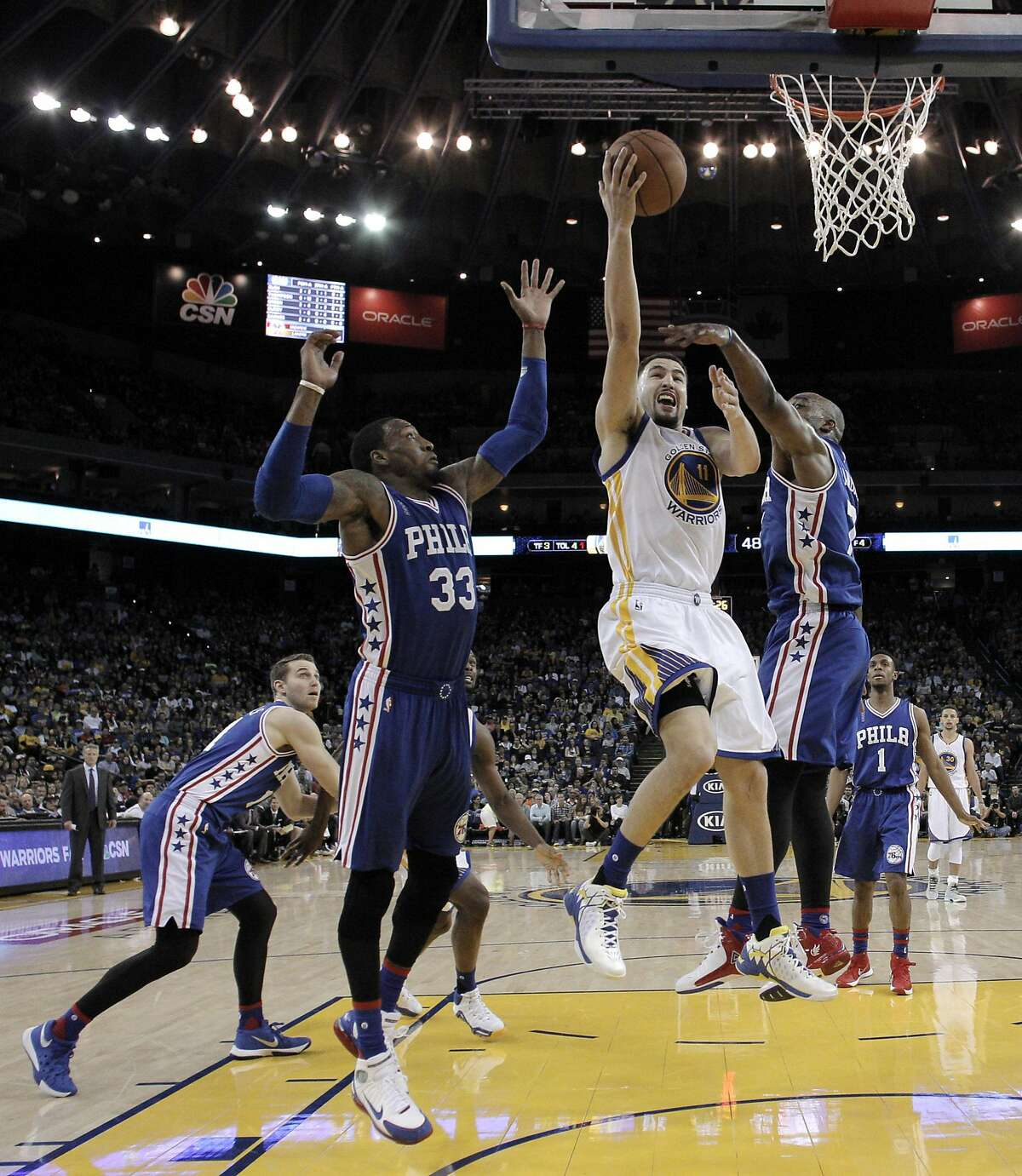 Klay Thompson (11) splits the defenders going in for a layup in the first half as the Golden State Warriors played the Philadelphia 76ers at Oracle Arena in Oakland, Calif., on Sunday, March 27, 2016.
