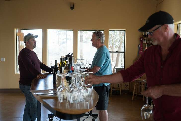 Left to right, Scott Ferguson speaks with Charles Dooly as Steve Moore cleans wine glasses at Moore Wine in Kelseyville, Calif. on Saturday, March 26, 2016. The tasting room is at 3,000 feet.
