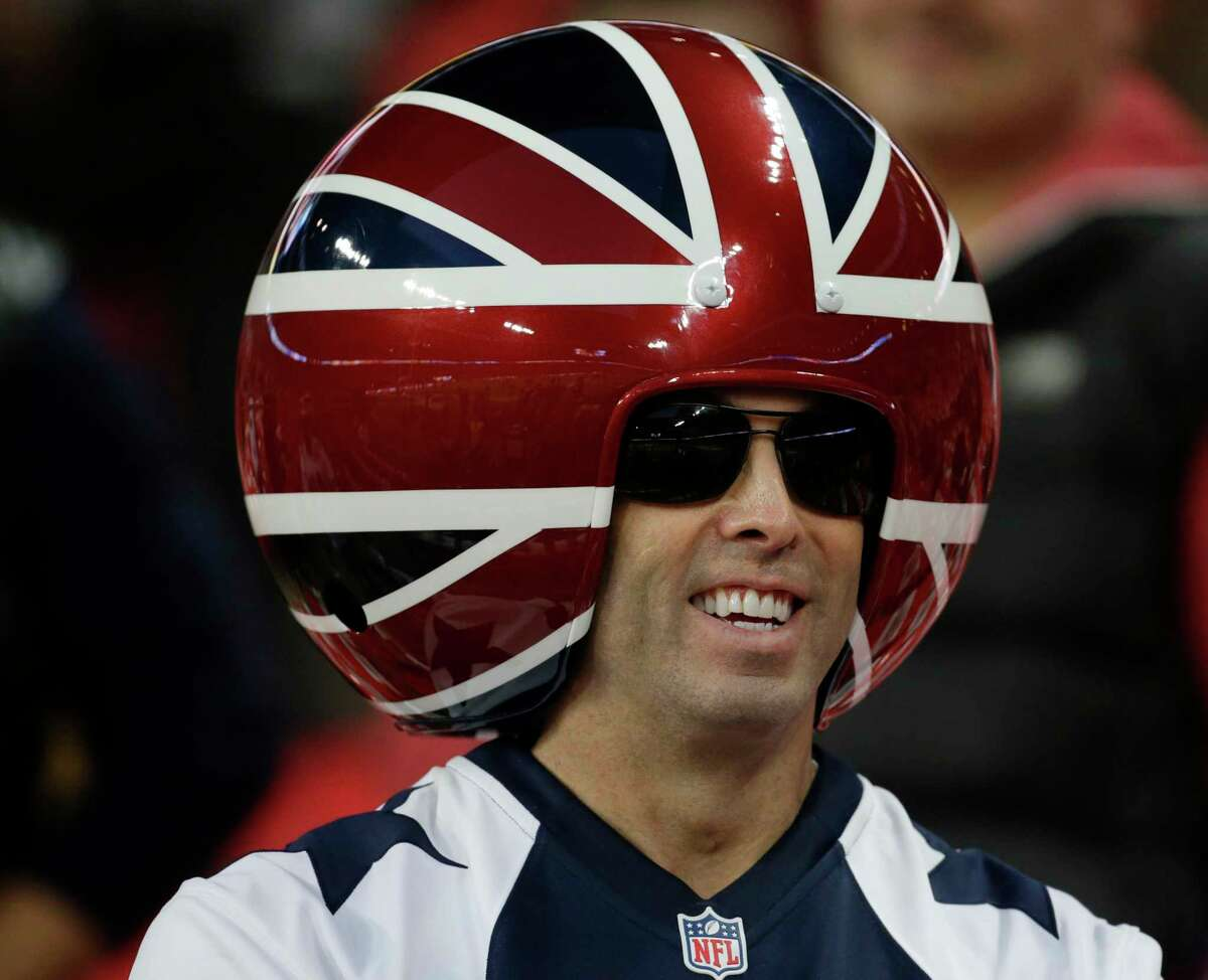 A spectator wears a ball shaped helmet before the NFL football game between the Dallas Cowboys and the Jacksonville Jaguars at Wembley Stadium in London, Sunday, Nov. 9, 2014. (AP Photo/Matt Dunham)