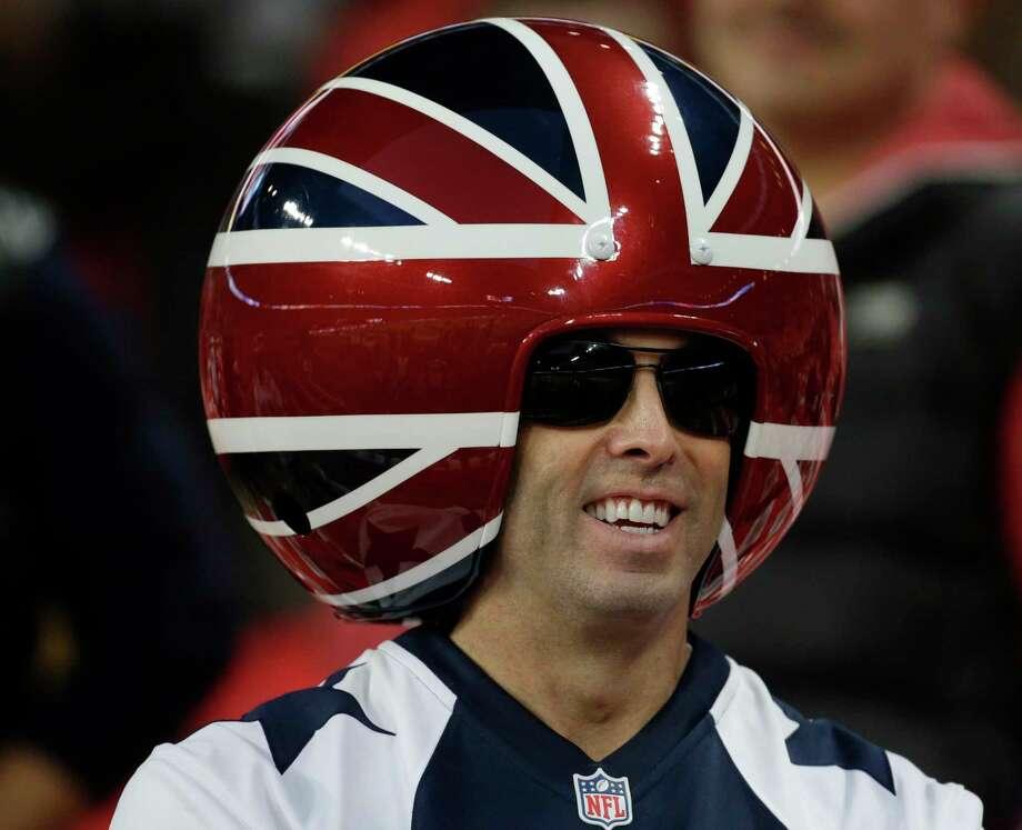 A spectator wears a ball shaped helmet before the NFL football game between the Dallas Cowboys and the Jacksonville Jaguars at Wembley Stadium in London, Sunday, Nov. 9, 2014.  (AP Photo/Matt Dunham) Photo: Matt Dunham, Associated Press / AP