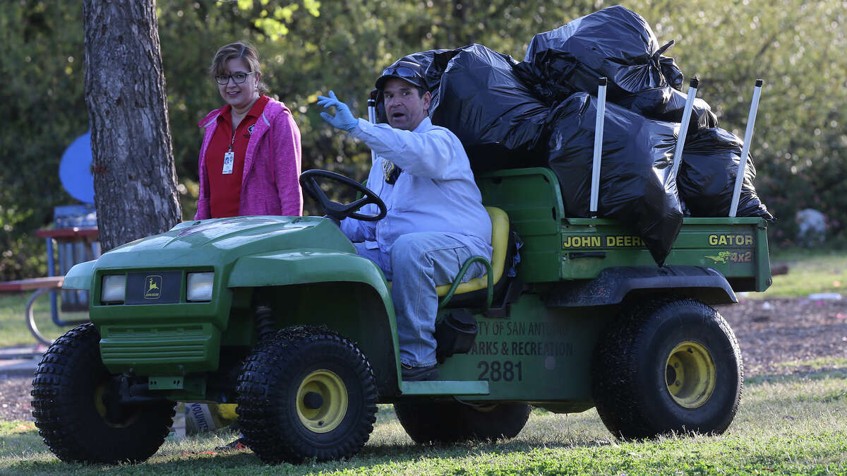 City of San Antonio employees Laura Gomez (left) and Phillip John Martinez talk while picking up trash Monday March 28, 2016 at Brackenridge Park after the long Easter weekend. The city allows camping at Brackenridge and other area parks Easter weekend resulting in a high accumulation of trash.