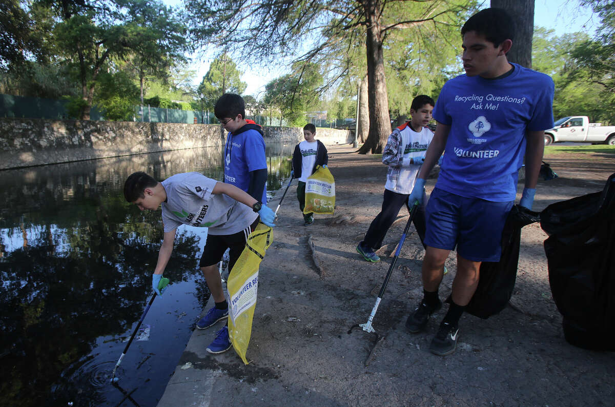Volunteer Adrian Cano (left) picks up trash Monday March 28, 2016 at Brackenridge Park after the long Easter weekend. The city allows camping at Brackenridge and other area parks Easter weekend resulting in a high accumulation of trash. Cano was picking up trash with volunteers from Central Catholic High School.