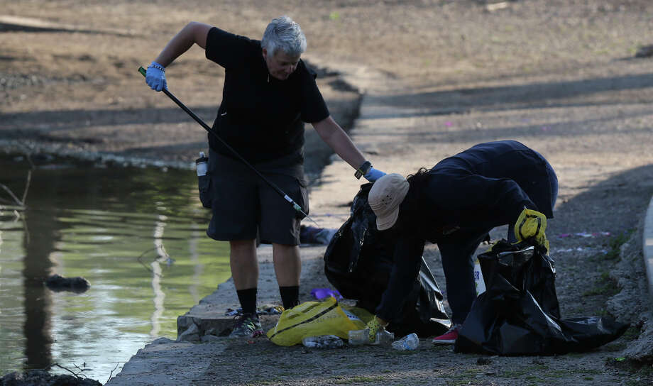 Volunteers from Kohl's department store pick up trash Monday March 28, 2016 at Brackenridge Park after the long Easter weekend. The city allows camping at Brackenridge and other area parks Easter weekend resulting in a high accumulation of trash. Photo: John Davenport, San Antonio Express-News / ©San Antonio Express-News/John Davenport
