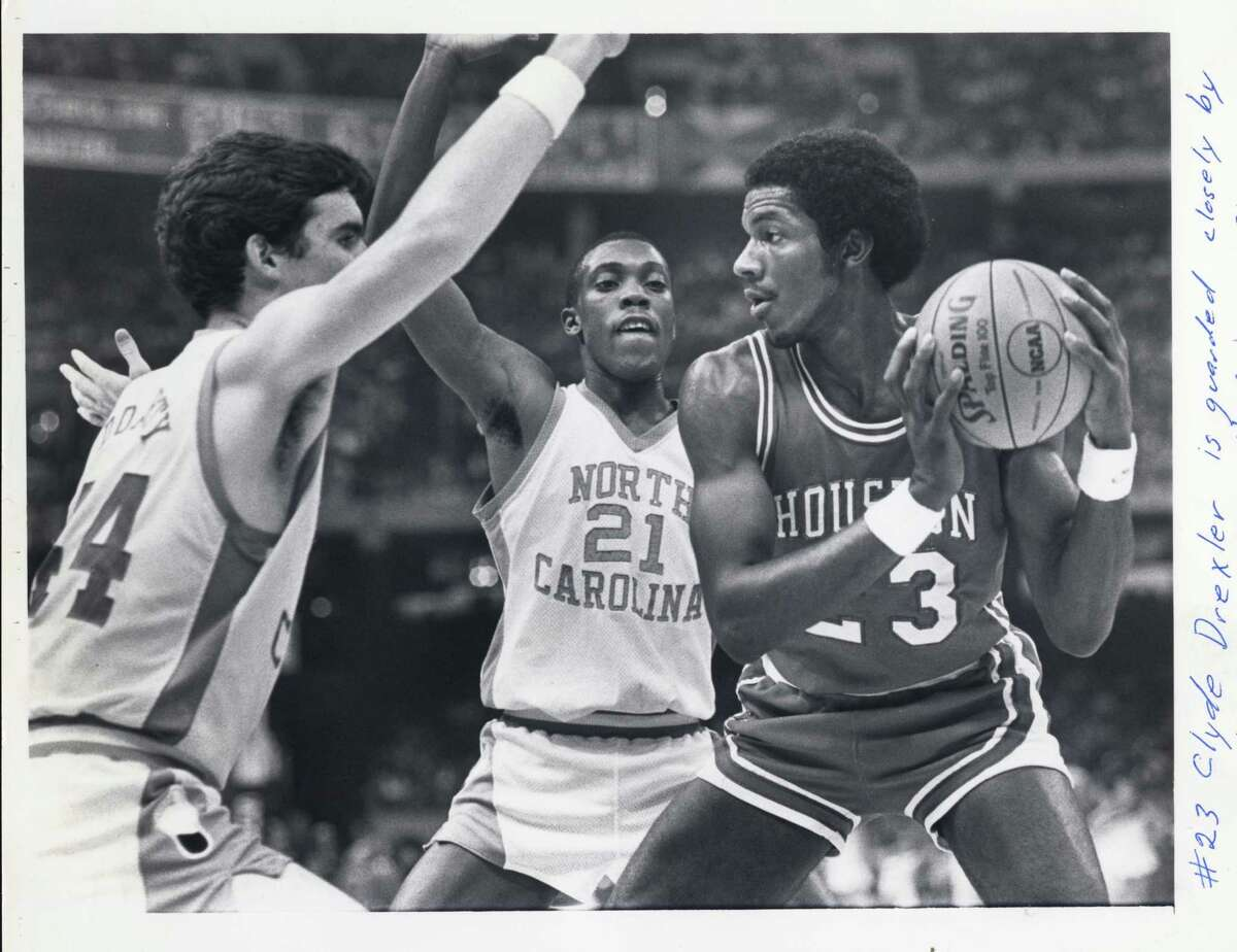 PHOTO FILED: UNIVERSITY OF HOUSTON BASKETBALL. 03/27/1982 - UH's #23 Clyde Drexler is guarded closely by North Carolina's #44 Matt Doherty and #21 Jimmy Black in the semifinal of the 1982 NCAA Men's Division I Basketball Tournament in the Superdome in New Orleans, LA. Steve Campbell / Houston Chronicle