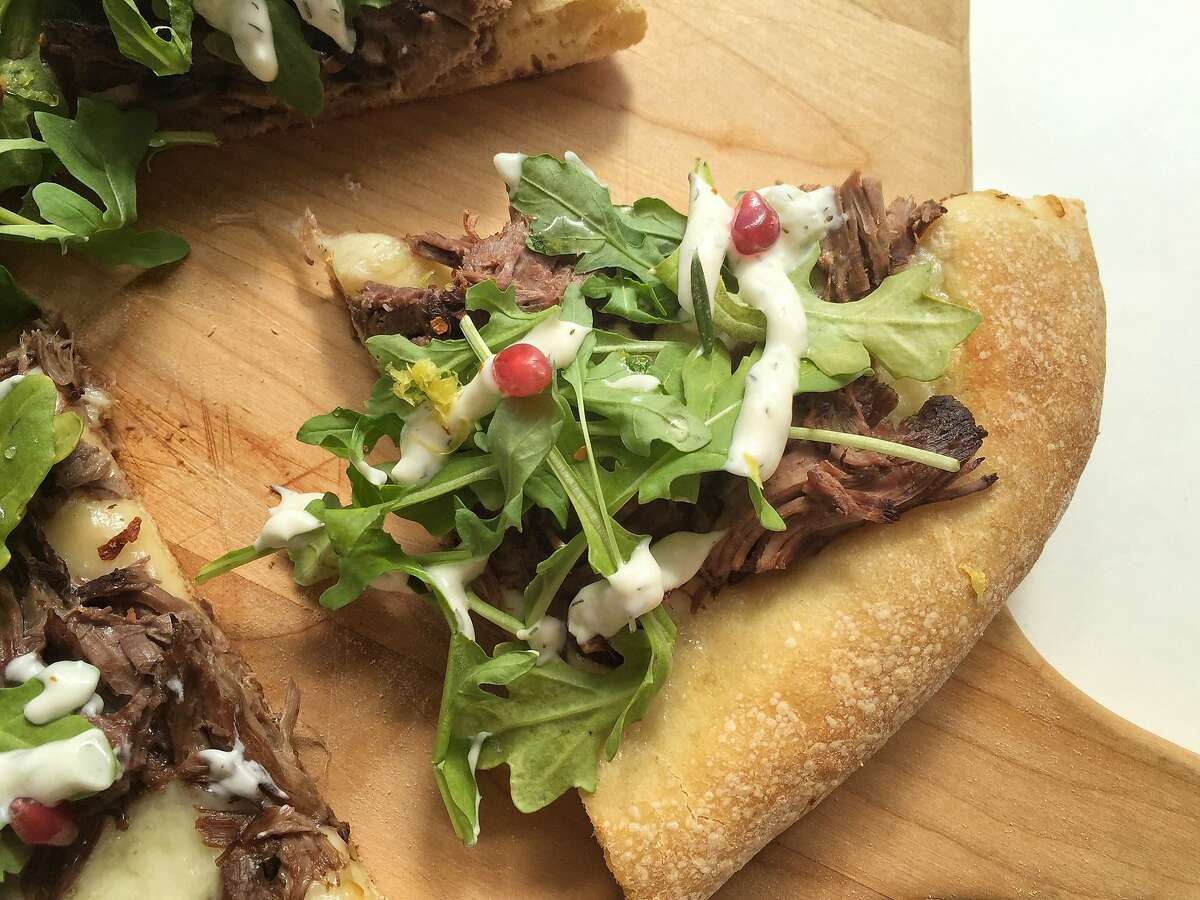 Pizza with spicy braised lamb, tzatziki, arugula and rosemary syrup from Laura Meyer